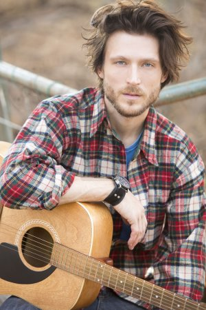 Photo for Portrait of scruffy man with a guitar - Royalty Free Image