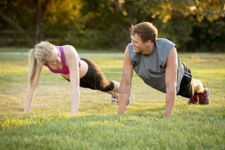 Photo for Happy young couple exercising together in a park - Royalty Free Image