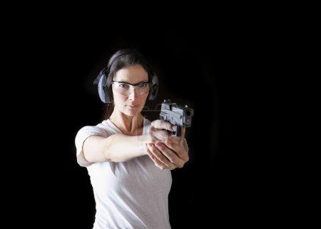 Photo pour Femme tenant un pistolet avec un équipement de protection - image libre de droit