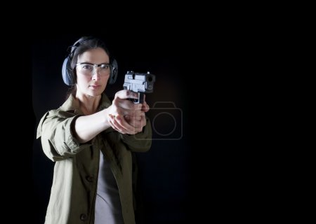 Photo for Woman holding a gun with protective gear - Royalty Free Image