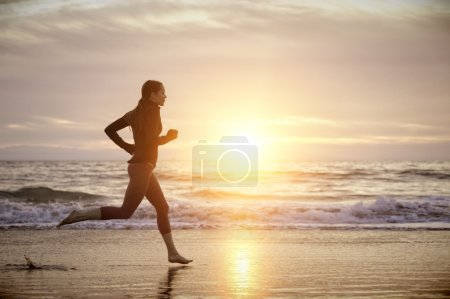 Photo for Woman running on the beach at sunset - Royalty Free Image
