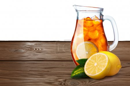 Photo for Jug or pitcher of iced tea with lemons on foreground standing on wooden table. Clipping paths for both background and pitcher, infinite depth of field - Royalty Free Image