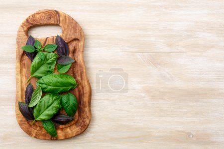 Photo for Heirloom basil on olive wood cutboard. The cultivars including Genovese, Holy Basil, spice globe. Flat lay, above view - Royalty Free Image
