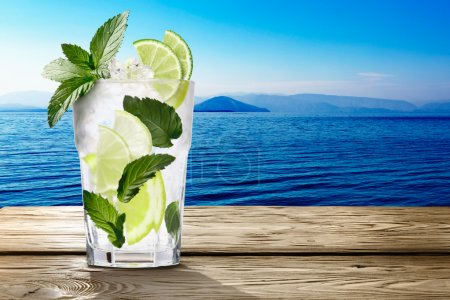 Photo for Mojito (alcoholic cocktail with rum, lime and mint)  in wooden table against seascape. Clipping paths, infinite depth of field - Royalty Free Image