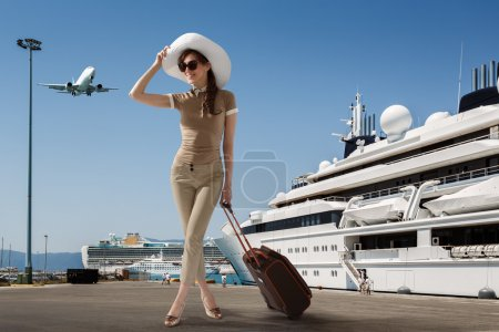 Photo for Stylish slim woman wearing sunglasses and white hat standing in seaport near docked cruise ship while smiling and holding her luggage on a summer sunny day. Travel, vacation, adventure concept. - Royalty Free Image