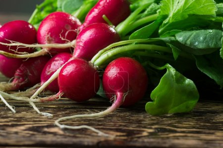 Photo for Bunch of fresh radishes on wooden table - Royalty Free Image