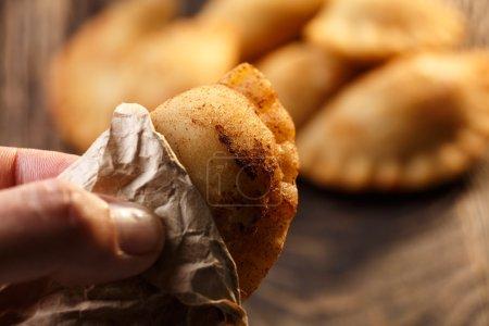 Male hand holding fried colombian empanada. Savory...