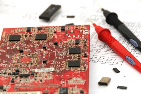Photo for Electronic circuit board with some elements, chips and test prods on circuitry documentation. Repairing and engineering process. - Royalty Free Image