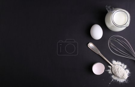 Baking ingredients on black background