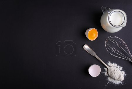 Photo for Baking ingredients - flour, milk, eggs with a whisk and spoon on black background - Royalty Free Image