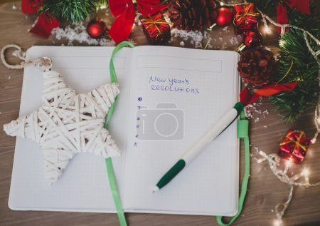 New year's resolutions written on a notepad with a star and new
