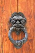 Tmavé dřevěné dveře s černou zaprášenou rukojetí