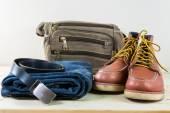 Zátiší s kostkované košile, džíny, hnědé boty a tašky na zalesněný