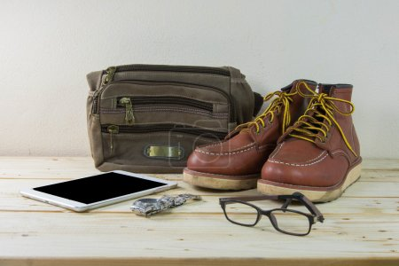 Still life with casual man, boots and bag on wooden table backgr