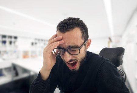 Young businessman yawning