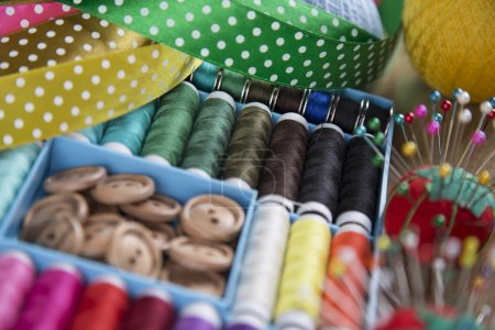 Sewing kit. Colored thread, pins, buttons, ribbons, safety pin.