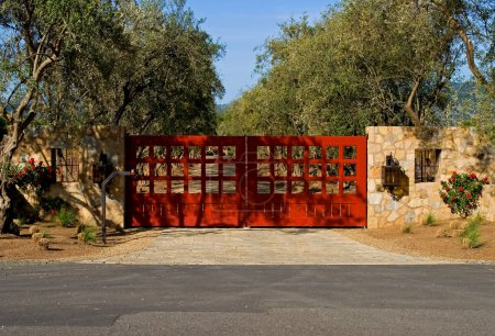 Photo for Private driveway with a big red gates at sunset - Royalty Free Image