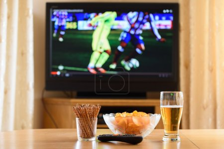 Television, TV watching (football, soccer match) with snacks lyi
