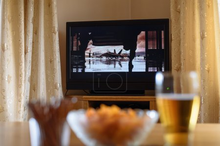 television, TV watching (movie) with snacks lying on table