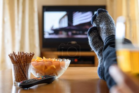 Television, TV watching (movie) with feet on table and huge amou