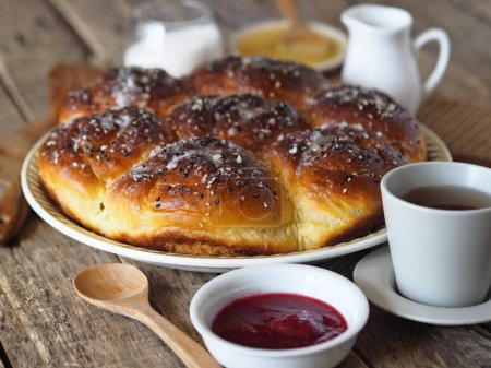 Photo for Homemade cake. Buns with jam filling, sprinkled with sesame and icing sugar, on an ancient wooden background, with ingredients and a Cup of tea - Royalty Free Image