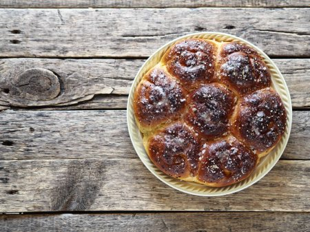 Photo for Close up view from above.Homemade buns with jam filling, sprinkled with sesame and icing sugar, on an ancient wooden background - Royalty Free Image