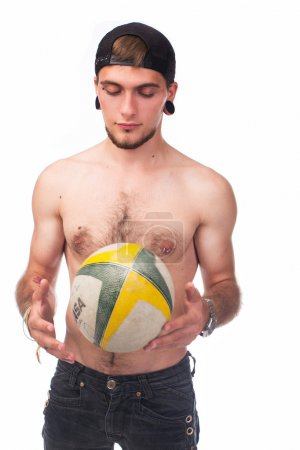 Man with tattoos and piercing holding ball
