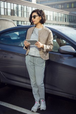 Photo for Full length portrait of young smiling woman in sunglasses with tablet standing near the car. Business concept - Royalty Free Image
