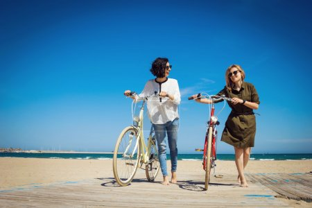 Two friends walking on the beach with bicycles