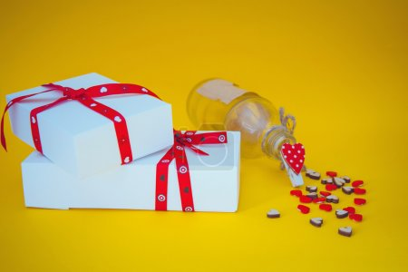 Gift boxes, hearts and bottle on yellow background