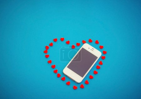White phone with red hearts on blue background