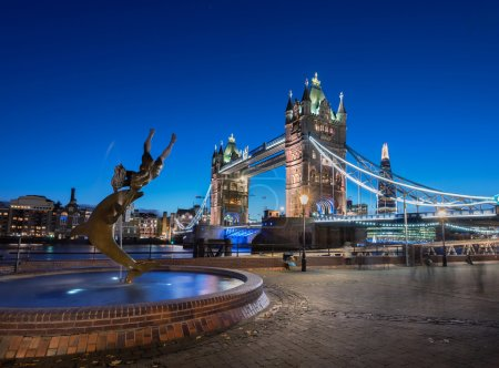 Photo for Tower bridge is the most iconic landmark of London, England. A fountain with statue of dolphin and a girl in the foreground. - Royalty Free Image
