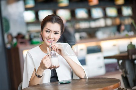 Photo for Beautiful woman drinking sweet drink in Cafe - Royalty Free Image