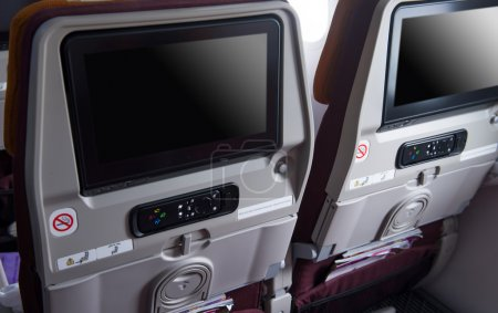 The Monitor and rremote on back seats in the cabin of the plane