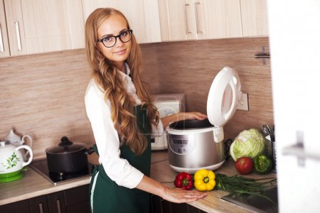 Photo for Beautiful girl in the kitchen with slo-cooker - Royalty Free Image