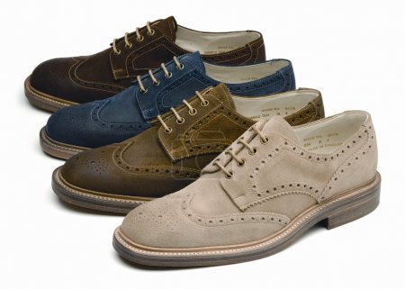 Suede mens shoes of different colors on a white ba...
