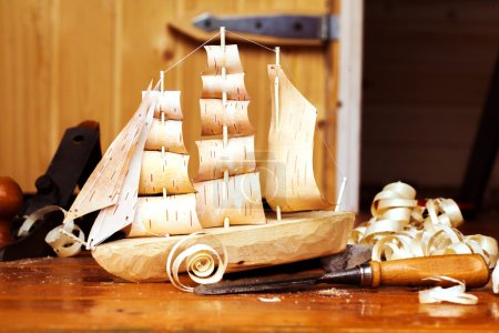 Wooden ship toy workshop carpenter with a plane, chips, birch bark, homemade