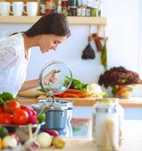 Mladá žena stojící sporák v kuchyni
