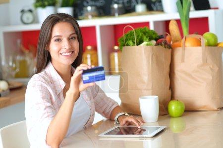 Photo pour Femme souriante, magasinage en ligne à l'aide de tablette et carte de crédit dans la cuisine . - image libre de droit