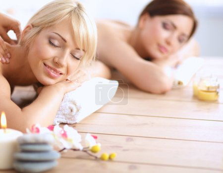 Two young beautiful women relaxing and enjoying at the spa center