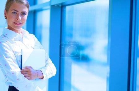 Photo pour Femme d'affaires debout contre la fenêtre du bureau tenant des documents en main  . - image libre de droit
