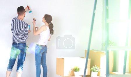 Photo pour Portrait de heureux sourire jeune couple peinture mur intérieur de la maison neuve . - image libre de droit