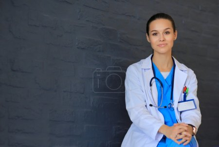 Young woman doctor sitting near wall