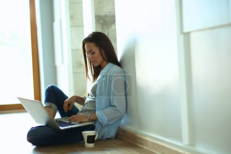 Young beautiful woman at home sitting on the floor with laptop