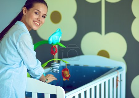 Young woman standing near childrens cot.