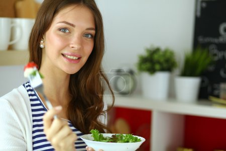 Photo for Young woman eating salad and holding a mixed salad - Royalty Free Image