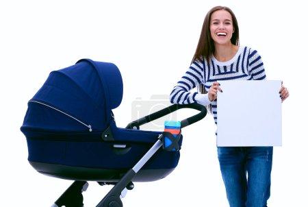 Photo pour Portrait de toute la longueur d'une mère avec une poussette maintenant vide, isolé sur fond blanc - image libre de droit