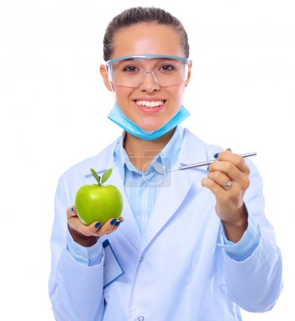 Dentist medical doctor woman hold green fresh apple in hand and mirror