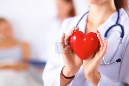 Young woman doctor holding a red heart, isolated on white backg