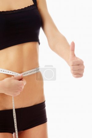 Woman measure her waist belly by metre-stick and showing ok